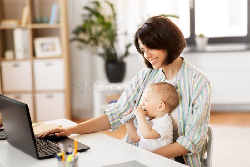 Arbetande mamman med behandla som ett barn pojken och b?rbara datorn hemma arkivbild