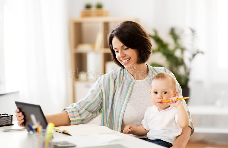 Arbetande mamman med minnestavlaPC och behandla som ett barn hemma arkivbild