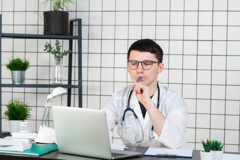 Arbetande nattetid för ung stilig doktor på sjukhuset arkivbild