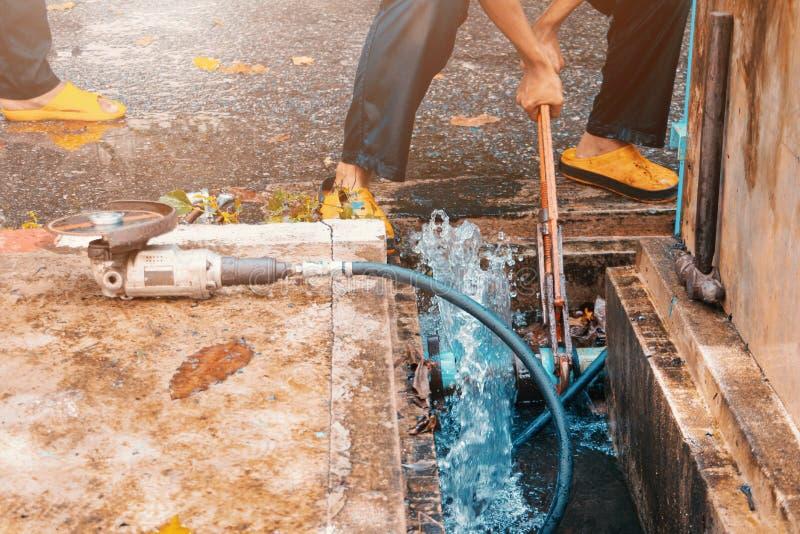 Arbetande reparation för rörmokare det brutna röret med justerbara skiftnycklar eller låsa plattång i håldike på vägren- och vatt royaltyfria foton