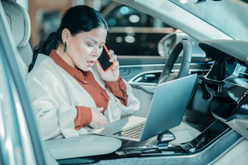 Arbetande sammanträde för kvinna på en chaufförplats av hennes bil fotografering för bildbyråer