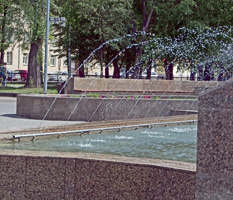 Arbetande springbrunn i stadsfyrkanten på en varm dag som flyger vattendroppar royaltyfria bilder