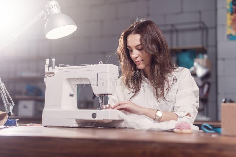 Arbetande sy för attraktiv Caucasian sömmerska med symaskinen på hennes arbetsplats i studiovindinre arkivbilder