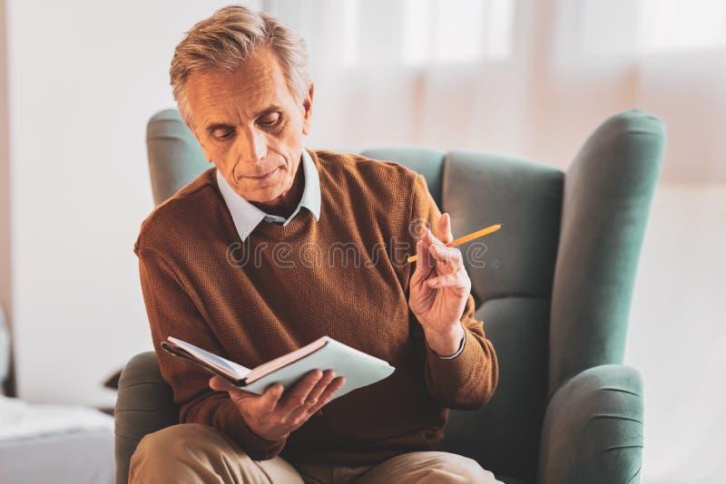 Arbetande upptaget ordnande schema för pensionärkänsla arkivfoto