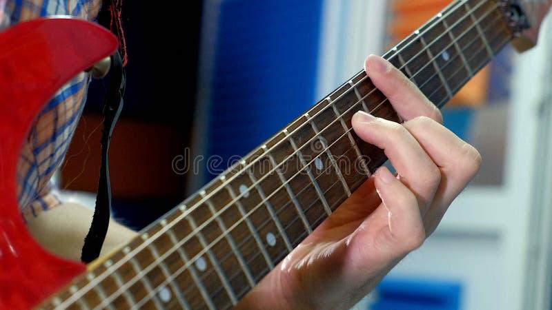 Arbetar den idérika musikern för mannen på studion, genom att spela, att sjunga och att anteckna gitarren med anteckningsboken oc arkivfoton