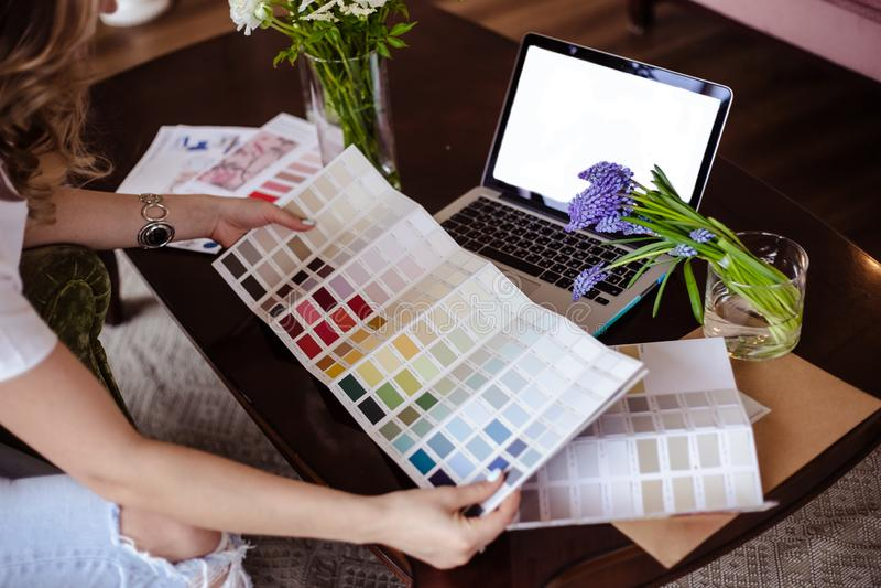 Arbetar den unga kvinnan för dekoratören med färgpaletten, tillfälligt foto för livsstil fotografering för bildbyråer