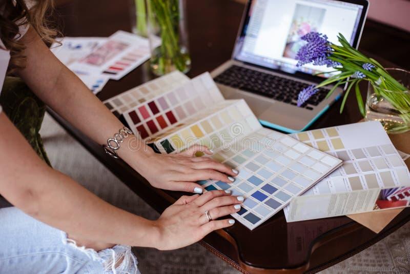 Arbetar den unga kvinnan för dekoratören med färgpaletten, tillfälligt foto för livsstil royaltyfria bilder