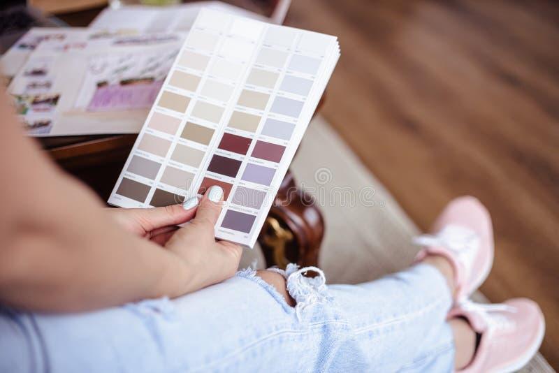 Arbetar den unga kvinnan för dekoratören med färgpaletten, tillfälligt foto för livsstil arkivfoto