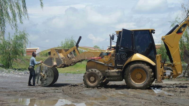 Arbetar- och grävskopaladdarbackhoe i konstruktionsplats arkivbild