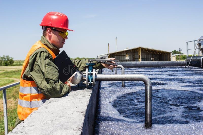 Arbetarbildskärm som filtrerar industriellt vatten arkivfoton