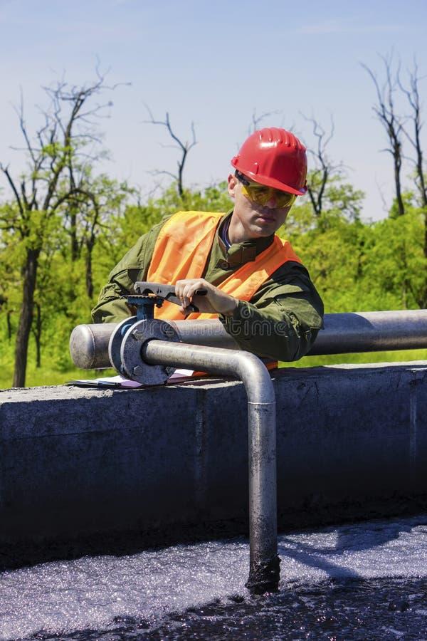 Arbetarbildskärm som filtrerar industriellt vatten arkivbild