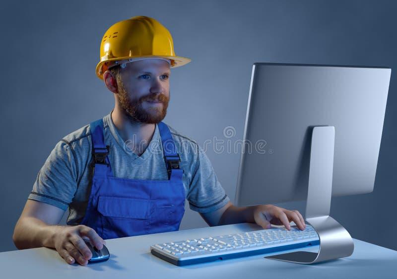 Arbetarbyggmästare i hjälmen och likformign som arbetar på en dator, purc arkivfoton