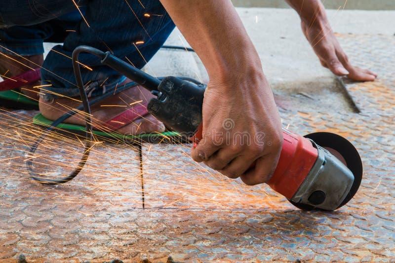 Arbetarcuttingmetall med grinderen malande järnsparks royaltyfria foton
