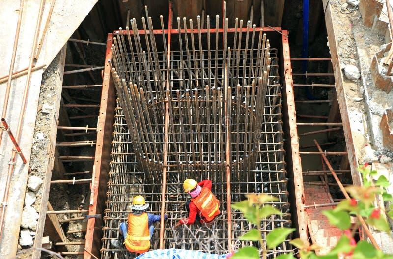 Arbetare arbetar på stålstänger på konstruktionsplatsen arkivfoton