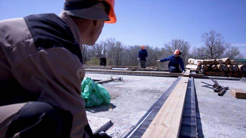 Arbetare av att mäta träbräden på konstruktionsplatsen gem Byggmästare gör mätningar av bräden för konstruktion av royaltyfria foton
