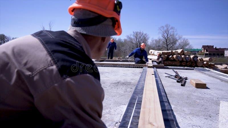 Arbetare av att mäta träbräden på konstruktionsplatsen gem Byggmästare gör mätningar av bräden för konstruktion av fotografering för bildbyråer