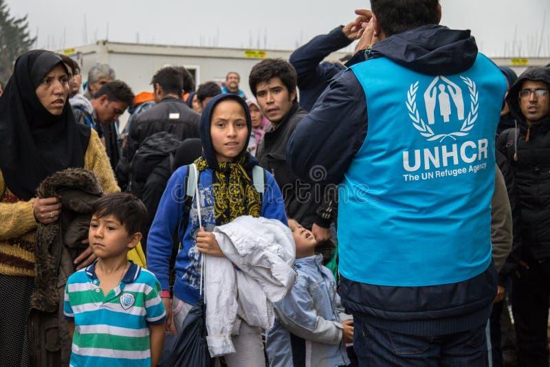 Arbetare av UNHCR, Förenta Nationernabyrån för flyktingar som klarar av en folkmassa av yougkvinnor på gränsen mellan Serbien & K royaltyfri foto