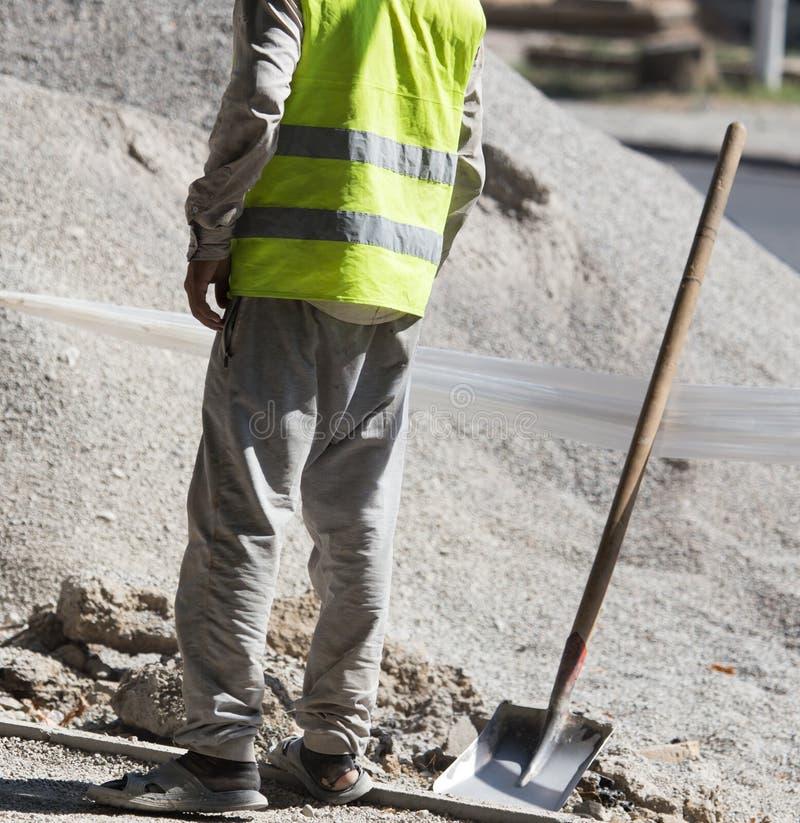Arbetare dubbar vägsand och grus royaltyfri bild