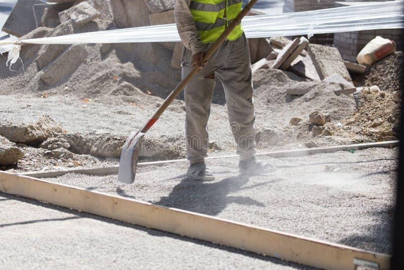 Arbetare dubbar vägsand och grus royaltyfri foto