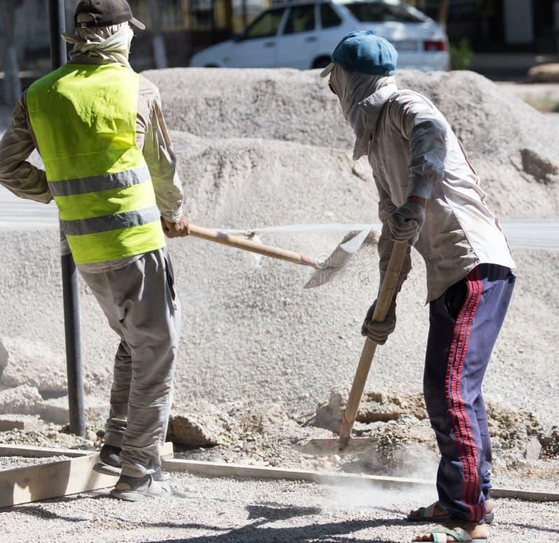Arbetare dubbar vägsand och grus royaltyfria bilder