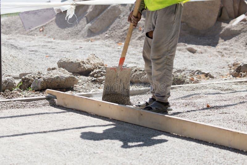 Arbetare dubbar vägsand och grus arkivfoton