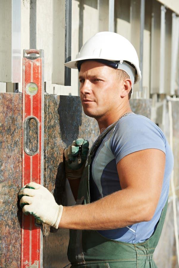 Arbetare för byggmästarefasadstuckatör med nivån royaltyfria foton