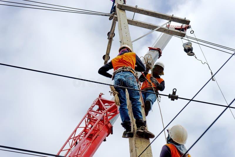 Arbetare för elektrikerlinjearbetarerepairman på klättringarbete på elektrisk stolpemaktpol royaltyfria bilder