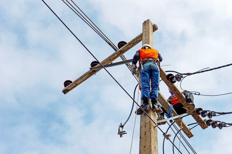 Arbetare för elektrikerlinjearbetarerepairman på klättringarbete på elektrisk stolpemaktpol royaltyfri fotografi