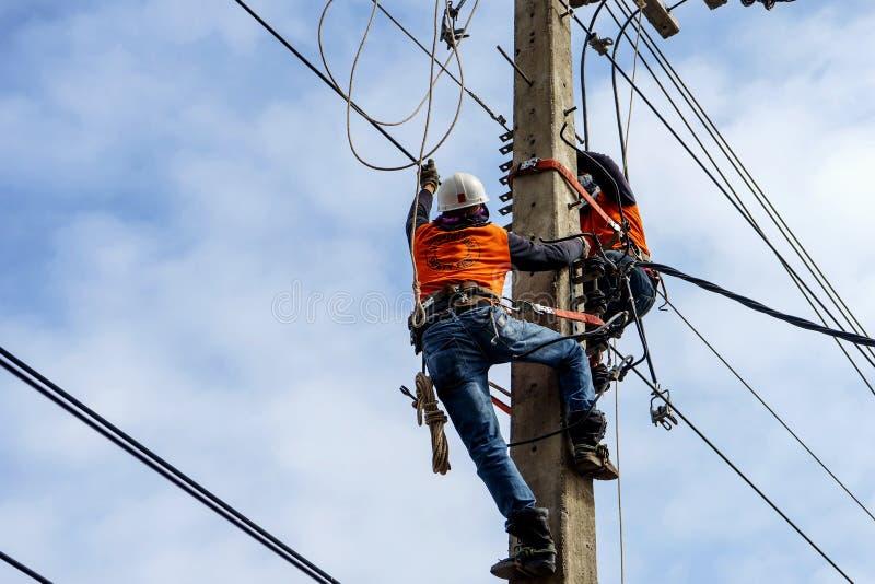Arbetare för elektrikerlinjearbetarerepairman på klättringen royaltyfri fotografi