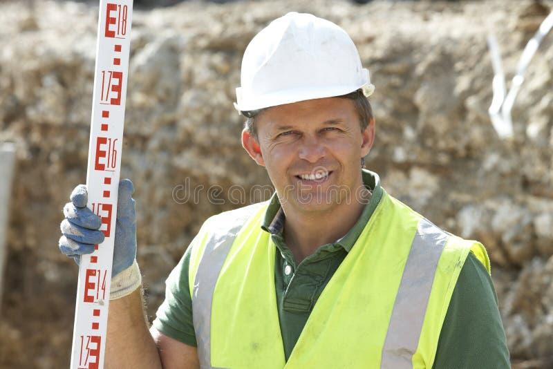 arbetare för konstruktionsholdingmått royaltyfri fotografi
