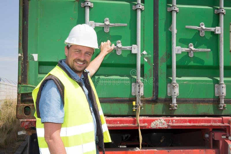 arbetare för konstruktionsplats som öppnar baksidan av en behållare på en lastbil royaltyfri fotografi