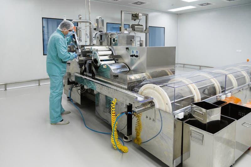 Arbetare för man för apotekbranschfabrik i skyddskläder i sterila arbetsförhållanden som fungerar på läkemedel royaltyfri bild
