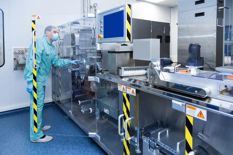 Arbetare för man för apotekbranschfabrik i skyddskläder i sterila arbetsförhållanden som fungerar på läkemedel royaltyfri foto
