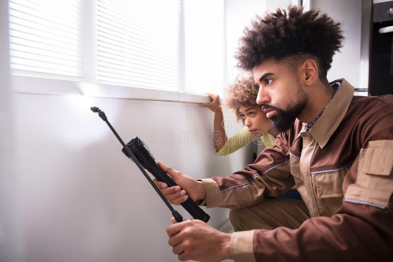 Arbetare för plågakontroll som använder facklan, medan bespruta insekticid royaltyfri foto