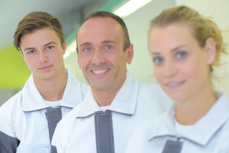 Arbetare för stående tre, i att matcha overaller royaltyfri foto