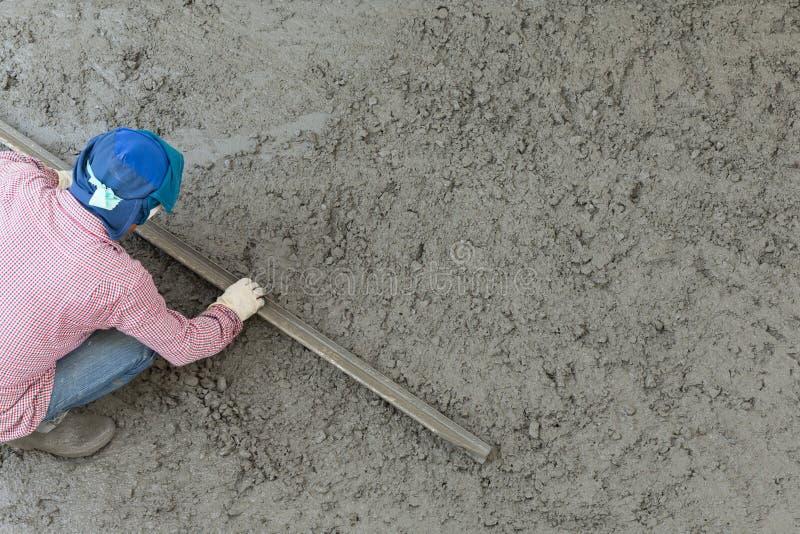 Arbetare för stuckatörbetongcement som rappar durken arkivbild