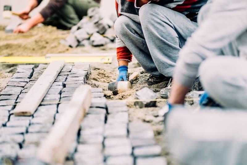 arbetare, faktotum och byggnadsarbetare som installerar kullerstentrottoar på banan, trottoaren eller vägen fotografering för bildbyråer
