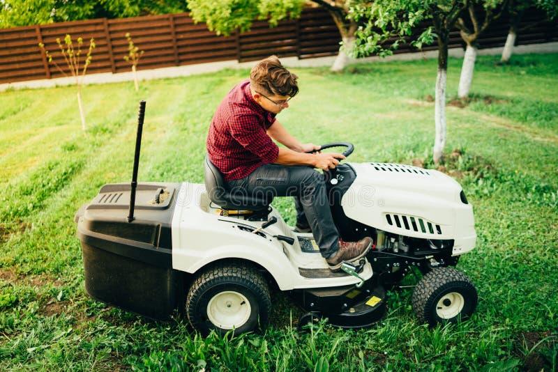 Arbetare faktotumbrämgräs genom att använda gräsklipparen royaltyfria foton