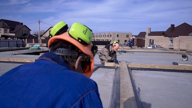 Arbetare gör mätningar som mäter bandet på konstruktion gem Byggmästare i likformign och den hårda hatten som arbetar på konstruk royaltyfri bild