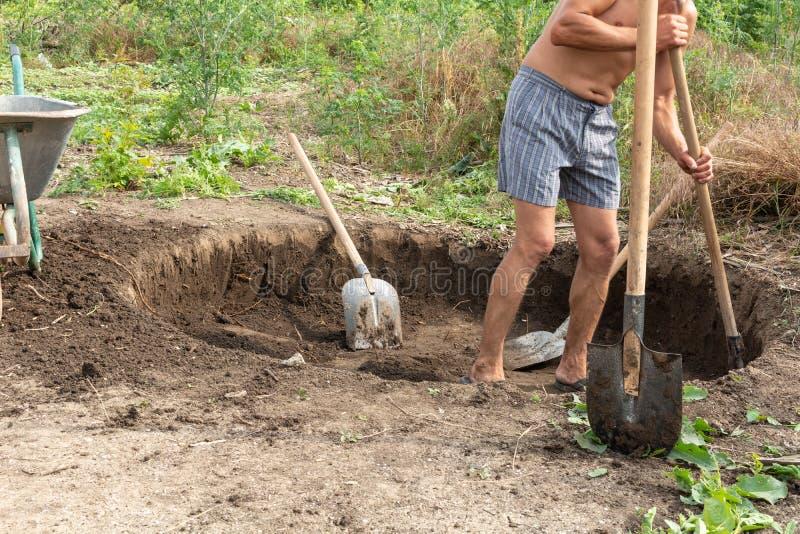 Arbetare gräver en grop för en septiktank royaltyfria bilder