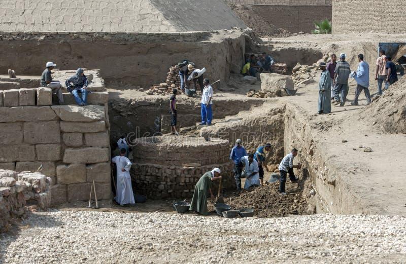 Arbetare gräver ett avsnitt av fördärvar närgränsande till ingången av den Karnak templet i Luxor, Egypten royaltyfria foton