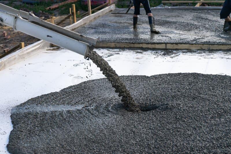 Arbetare häller fundamentet för konstruktionen av en bostads- byggnad genom att använda mobila konkreta blandare arkivfoto