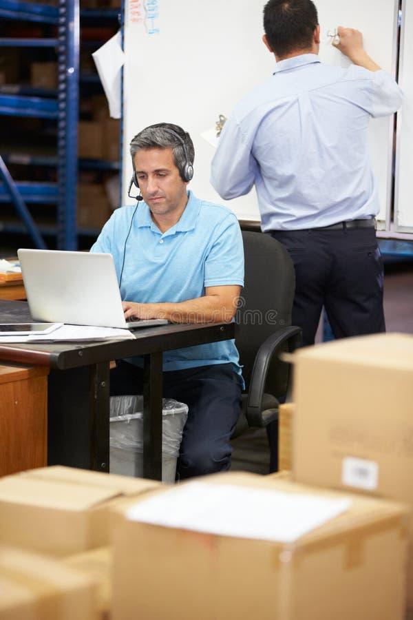 Arbetare i bärande hörlurar med mikrofon för lager och användabärbar dator royaltyfria bilder