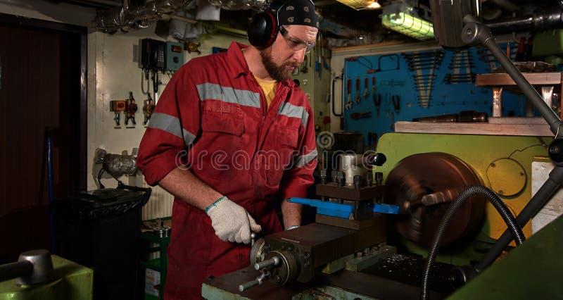Arbetare i den röda likformign som fungerar i manuell drejbänk i stort seminarium för metall arkivbild