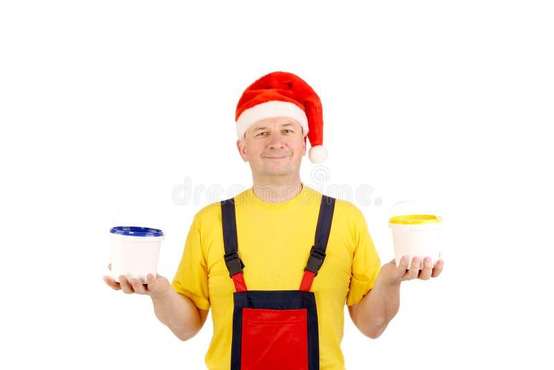 Arbetare i den santa hatten med två hinkar arkivbilder
