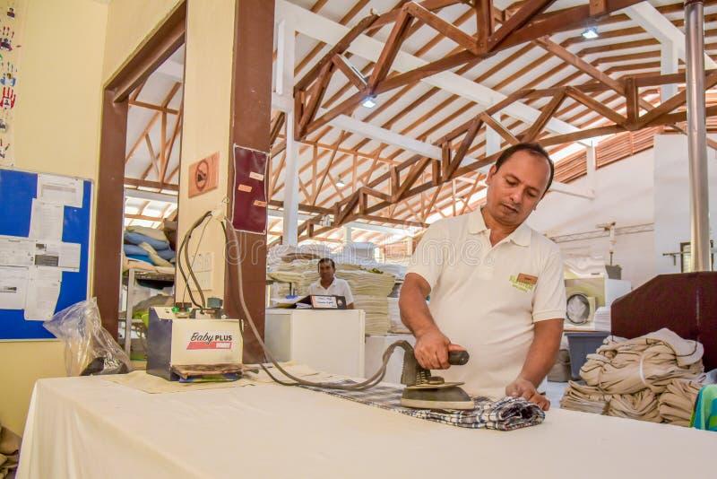 Arbetare i enhetlig stryka kläder i tvätterit royaltyfri fotografi