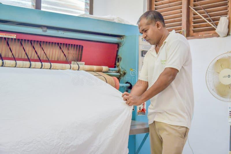 Arbetare i enhetligt stryka sängark genom att använda den speciala maskinen fotografering för bildbyråer