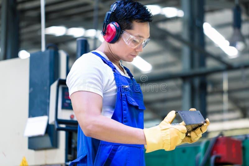 Arbetare i industriell fabrik som kontrollerar arbetsstycket royaltyfri fotografi