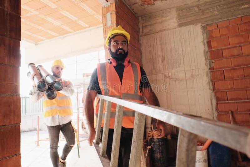 Arbetare i konstruktionsplats genom att använda hjälpmedel och tung utrustning fotografering för bildbyråer