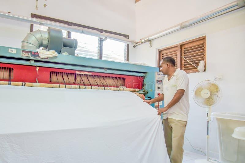 Arbetare i likformig som stryker sängark genom att använda den speciala maskinen royaltyfria bilder